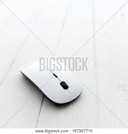 White computer mouse with pad on a wooden background