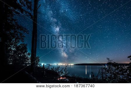 amazing view of starry night sky and citylights on the background reflected in river