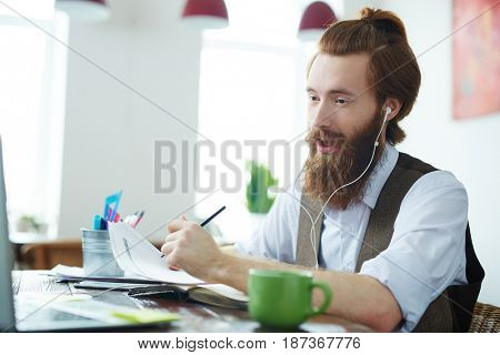 Portrait of trendy bearded man video chatting with business partners working in modern office