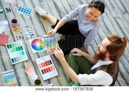 High angle view of creative designers team working in modern studio sitting on wooden floor and  discussing projects color scheme, smiling cheerfully