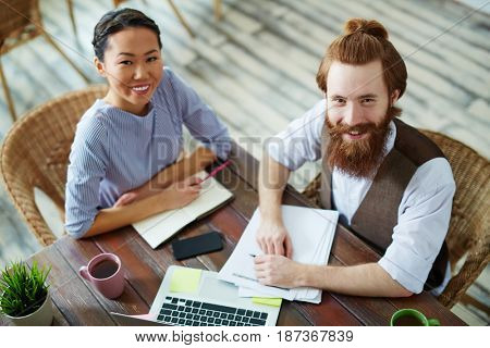 High angle portrait of casual business people, Asian woman and bearded man, looking up at camera and smiling during work meeting in creative studio