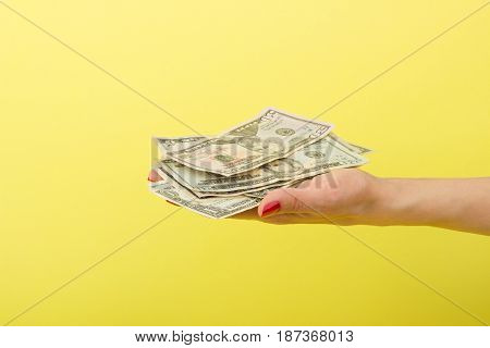 Fifty, Twenty, Five And One Dollars In The Woman's Hand, Yellow Background