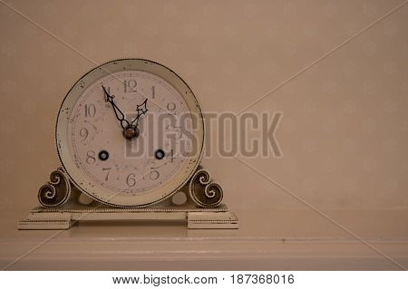 Old beige analog clock on the table
