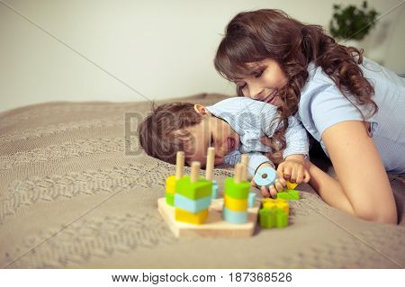 Young Mom And Young Son Sitting On The Bed. Mom Plays With Her Son. Family.