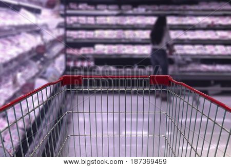 Shopping cart view in Supermarket Aisle with product shelves in blurry for background.