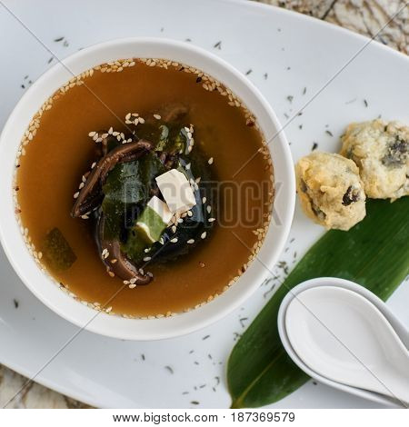Japanese cuisine. Delicious miso soup with shiitake mushrooms served in white ceramic bowl with spoon, green leaf, salt shaker and pepper-castor