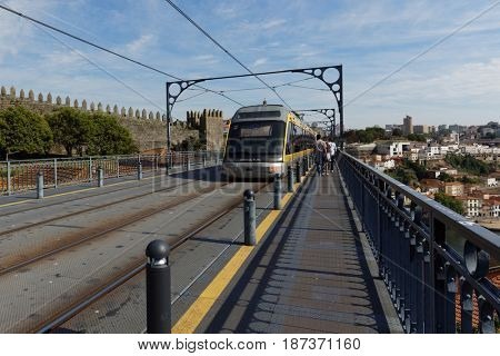 PORTO, PORTUGAL - MAY 8, 2017: People and metro train on the Dom Luis I Bridge. This double-deck metal arch bridge was built in 1881-1886