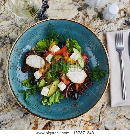 Greek salad with giant olives and provencal herbs served in blue ceramic plate with glass of white wine on marble table. Top view or flat lay.