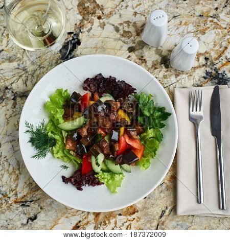 A warm salad of aubergines or eggplants and fresh vegetables served on white plate with glass of wine. Top view or flat lay.