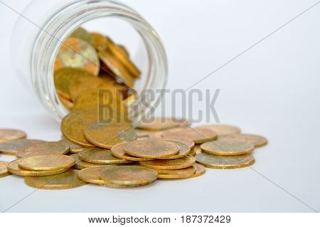 gold coin pour from glass bottle on white background
