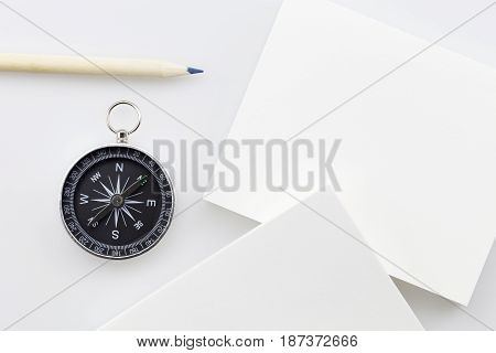 compass with blank white business paperpencil on white backgroundBusiness direction concept
