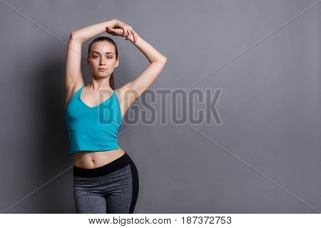 Slim young woman, fitness warm up at studio background, copy space. Pretty girl in fitwear at gray