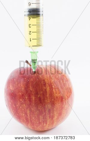 Red apple with a syringe containing a yellow liquid.