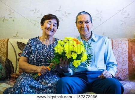 Grandfather with a grandmother and a bouquet of flowers. Smiling old people. Grandpa is holding a bouquet of yellow chrysanthemums.