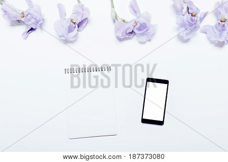 Mobile Phone, Notebook And Blue Flowers Lie On A White Background