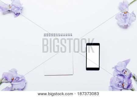 Mobile Phone, Blue Flowers And A Notepad Lying On A White Background