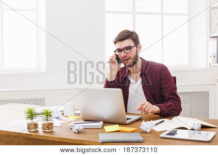 Office call. Young businessman in casual has mobile phone talk in modern workplace interior.