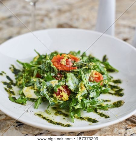 Salad with couscous, cherry tomatoes, avocado and mozzarella served on white plate. Salt shaker, pepper-castor and knife and fork on napkin on marble table