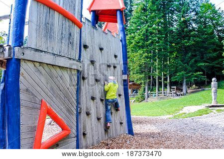Child climbs the wall. Child in the playground.