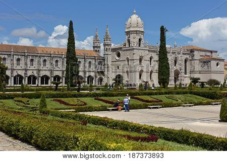 LISBON, PORTUGAL - MAY 11, 2017: People on the Praca do Imperio in front of Jeronimos Monastery. Since 1983, the monastery is listed as UNESCO World Heritage site