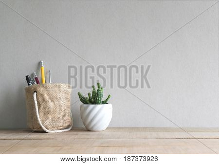 Cactus Flower With Pen And Pencil In Holder Basket On Wood Table.