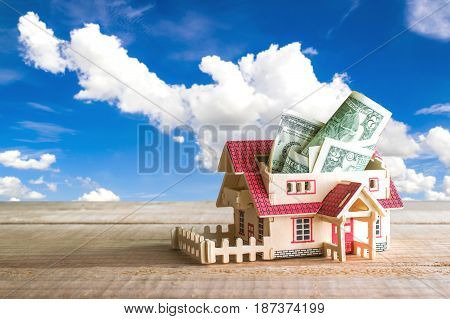 Wooden Model House With Money Inside On Wood Table With Copy Space Ready For Your Design.