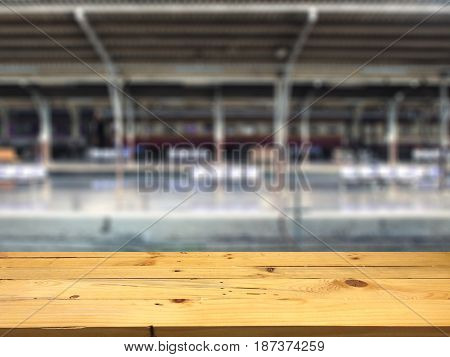 Empty wooden table space platform and blurred Train station platform background for product display montage.