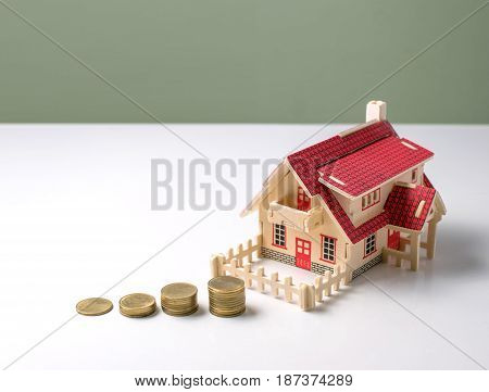 Wooden Model House With Money On White Table With Copy Space Ready For Your Design.