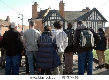 Crowd of tourists listen to tour guide in York city street