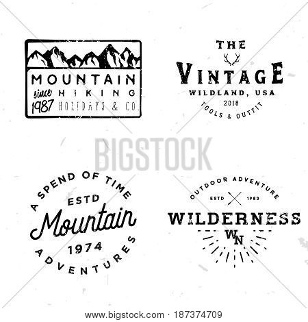Bundle of wilderness badges, logos, design elements (mountain shapes, arrows, deer antlers). Vintage retro styled stock vector illustration