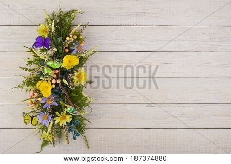 Colorful composition made of artificial flowers, fruits, butterflies, birds and ears of wheat in stylish vase on white woden background.