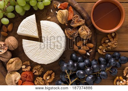 Cheese platter top view with fruits, homemade indian paneer cheese on wooden board with grapes and nuts, close-up