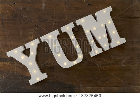 Led-illuminated Letters Spelling Yum On A Wooden Surface
