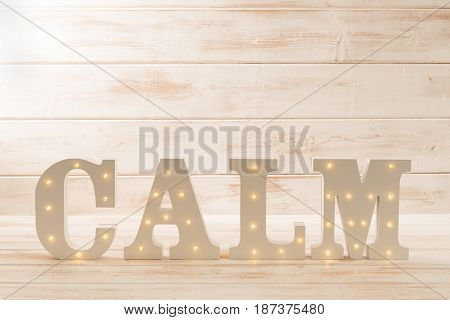 Illuminated Letters Spelling Calm Over Wooden Panel Background