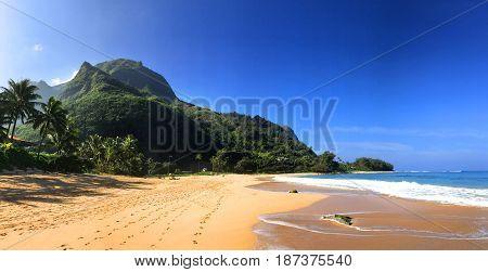 Golden sand and lush jungle mountains of Tunnels Beach Kauai Hawaii