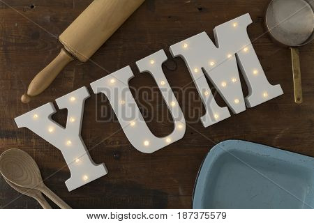 Led-illuminated Letters Spelling Yum Surrounded By Cooking Tools