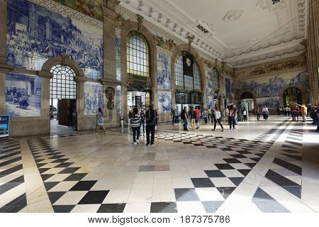 PORTO, PORTUGAL - MAY 8, 2017: People in the vestibule of Sao Bento Railway Station. It is decorated with approximately 20,000 azulejo tiles, dating from 1905â??1916
