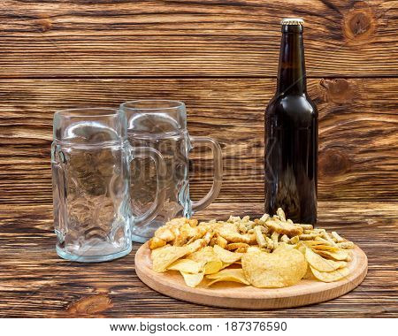 Bottle of beer with empty goblets and salty snacks on the table.