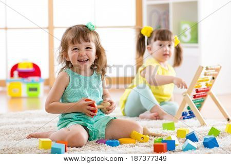 Children toddlers girls play logical toy learning shapes arithmetic and colors at home kindergarten or nursery