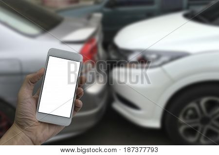 Hand holding smartphone with white blank screen blurred background car accidents.