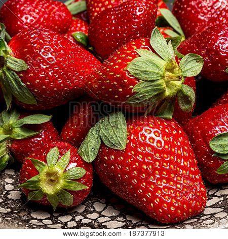 fresh ripe useful fruit strawberry in a clay bowl closeup