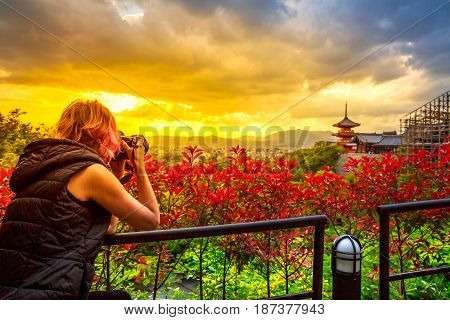 Travel woman photographer with professional camera takes shot of Kiyomizu-dera Temple with red pagoda at sunset light in spring time. Scenic aerial cityscape of Kyoto, Japan. Asian traveler concept.