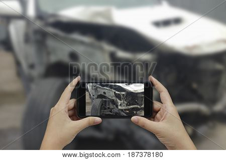 Hand holding smart phone take a photo at The scene of a car crash car accident