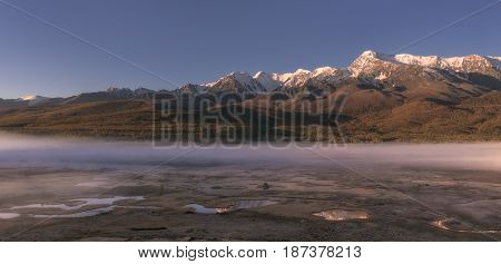 Sunrise in the mountains, the morning haze spreads over the earth, Altai region, Siberia, Russia