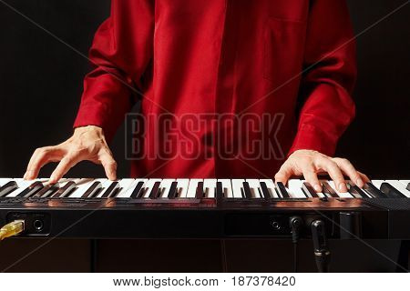 Musician playing the digital piano on a black background