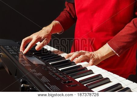 Pianist play the keys of the electronic synth on a black background