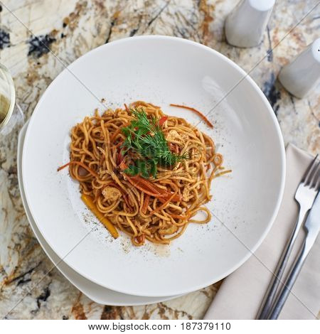 Flat egg noodles with vegetables served in big white ceramic round plate with glass of white wine on marble table