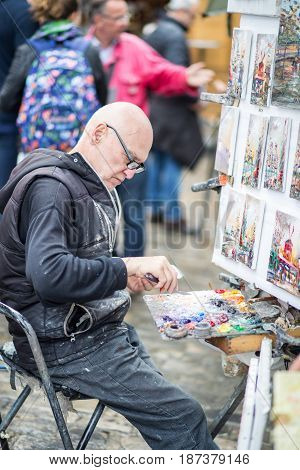 Paris, France - May 12, 2017: An artist painting on Place du Tertre in Montmartre district in Paris