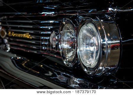 STUTTGART GERMANY - MARCH 04 2017: Headlamp of full-size car Pontiac Bonneville 1960. Close-up. Europe's greatest classic car exhibition