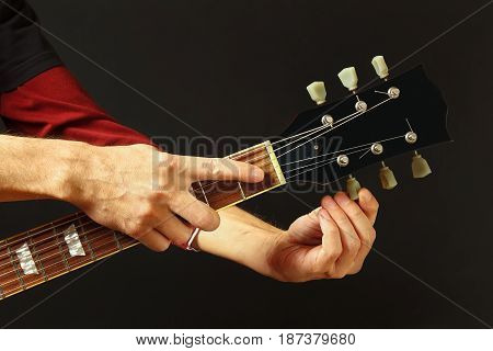 Hands of artist tunes the guitar on a dark background